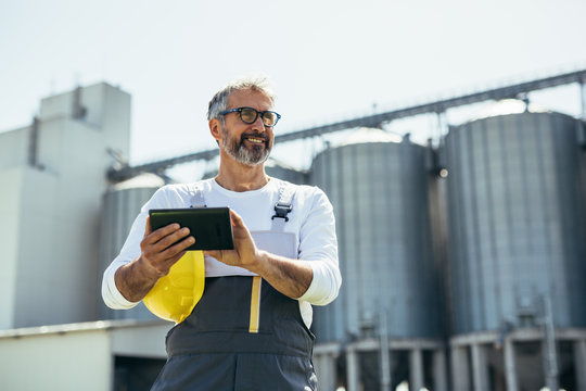 engineer using tablet in front of blurred grain silos
