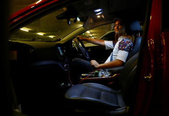 Musician Peter Huang poses for a photo inside his Hyundai Ioniq Electric car in Singapore