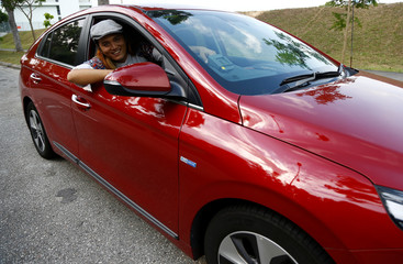 Musician Peter Huang poses for a photo with his Hyundai Ioniq Electric car in Singapore