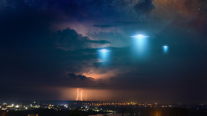 Extraterrestrial aliens spaceship fly above small town, ufo with blue spotlights in dark stormy sky.