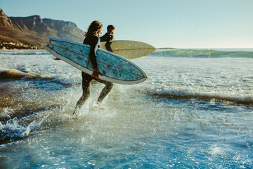 To young surfers going for water surfing