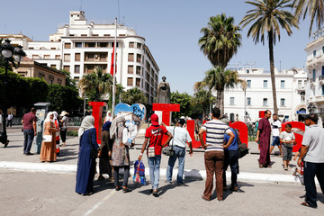 People pose for pictures at Habib Bourguiba avenue, the day after the death of Tunisian President Beji Caid Essebsi in Tunis