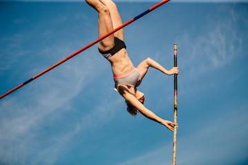 women pole vault athletics competition background blue sky.