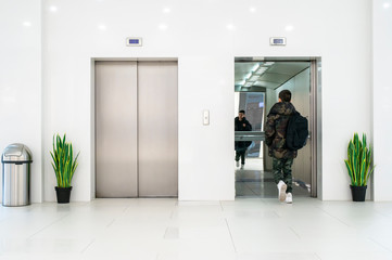 Teenager boy with casual clothes and white sneakers enters in elevator.