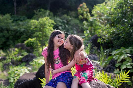 Sisters are exploring a tropical Hawaiian jungle.