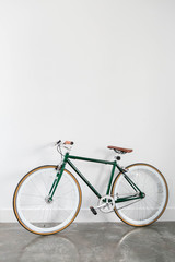 Foto op Aluminium Fiets Fixed Green and Brown Bicycle in Modern Home, Fixie Bike inside hous​e, white wall background, isolated retro bicycle