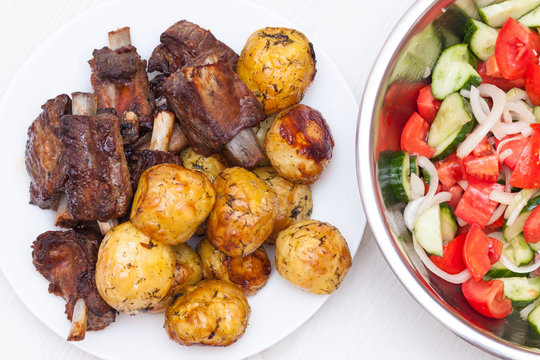 Sticky beef short ribs. BBQ ribs with potatoes and salad with tomatoes and cucumbers on white wooden background. Top view, flat lay.