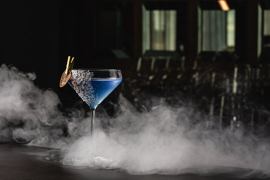 Aviation, drink with gin, lemon juice,maraschino liqueur and violette cream liquor. Garnished with lime chips and coconut crumbles. Place for text copy-paste on a black background and smoke for mystic