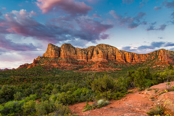 Sunset illuminates a beautiful vast landscape of red rock formations and green juniper tree forest below a blue sky with colorful pink and purple clouds - Sedona, Arizona