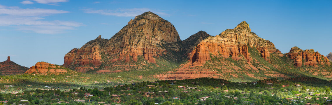 Beautiful panorama of colorful sandstone peaks and cliffs in early morning light above green trees, buildings and homes in the town of Sedona, Arizona
