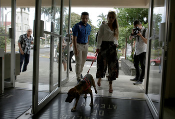 Isabella Aguilar with her dog Campeon (Champion) arrives in court for the trial of the dog's former owner in the first Costa Rica trial against the alleged animal abuser, in Atenas