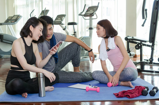 group of young sporty people using app on mobile phone together sitting on yoga mat in fitness gym after workout, exercise at morning, community, training, partnership, success and teamwork concept
