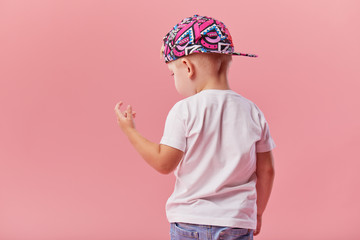 Little serious fashionable toddler boy in denim clothes and trendy cap. Isolated on pink background Wall mural