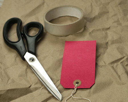 Scissors and red label on paper background