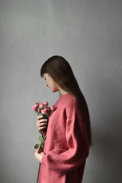 Side view of woman holding roses against gray wall