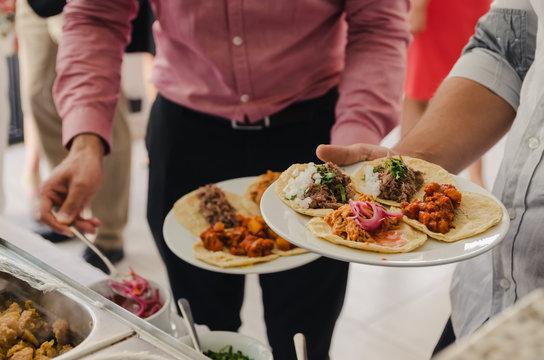 Hombres sirviendo comiendo tacos