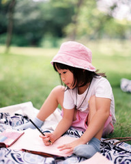 Asian little girl drawing a picture in the woods outdoors. 120 film shooting