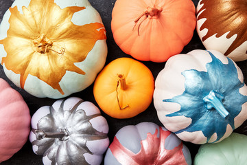 Bright pumpkins painted in different colors presented on a dark concrete background with reflection of shadows. Halloween card