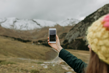 woman with smartphone taking photos at nature