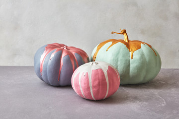 Composition of three different painted watermelons on a gray concrete background with copy space. Halloween
