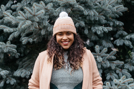 A beautiful woman decorating a pine tree with christmas ornaments in the snow