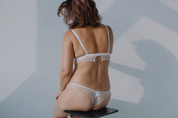 Unrecognizable real body type woman posing in lingerie by white wall