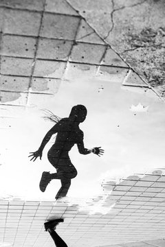 Reflection of woman running on street