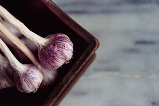 Close up of garlic bulbs on a wooden tray on a marble bench