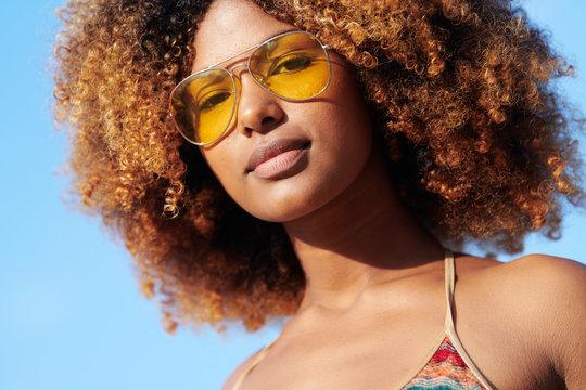 Confident black woman in sunglasses and bikini