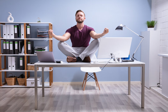 Businessman Meditating Over Desk