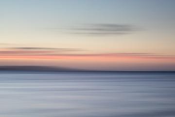The blurred wash of the sea's horizon at sunrise.