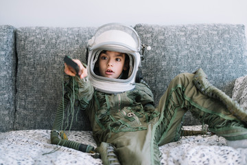 Amazed kid sitting on couch with a real astronaut uniform using a TV remote control