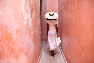 Rear view of woman walking through alley