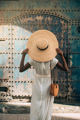 Rear view of woman in straw hat standing near old door