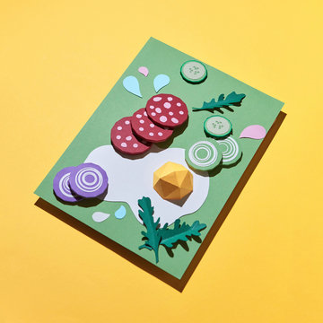 Paper craft food composition of pieces of salami, onion, cucumber, fried eggs and arugula on a green board on a yellow background with copy space.