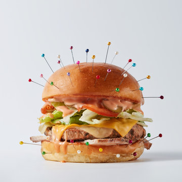 Burger as an object of a voodoo doll with needles for a ritual o