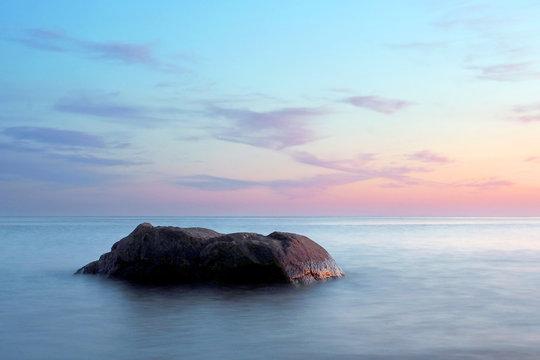 A stone in a calm sea at sunset