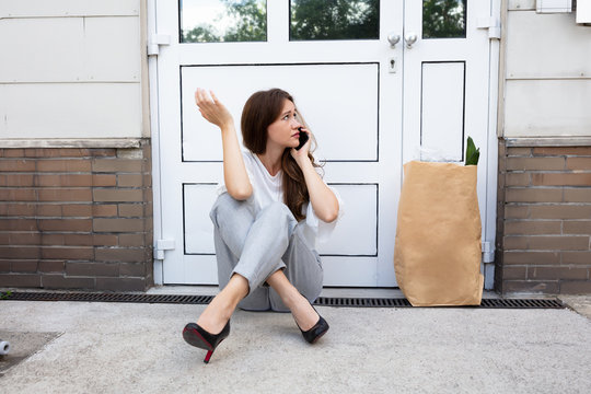 Young Woman Waiting In Front Of Closed Door