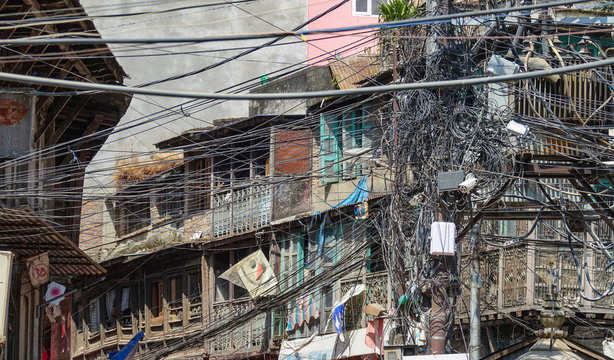 CLOSE UP: Wiring gets chaotically tangled up on the side of apartment building.