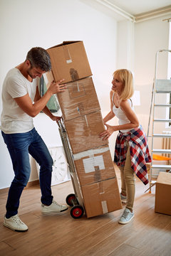couple with cardboard boxes while moving in house.