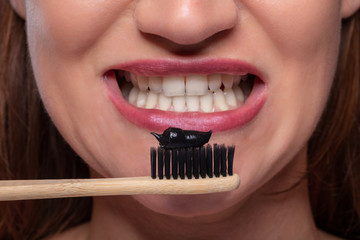 Woman Holding Tooth Brush With Black Active Charcoal Toothpaste