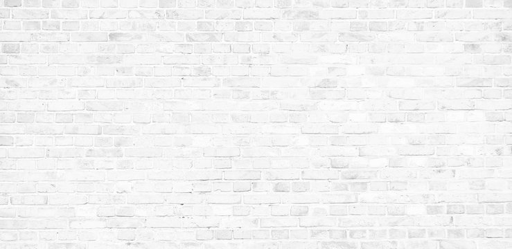 Simple white brick wall with light gray shades seamless pattern surface texture background in banner wide panorama format.