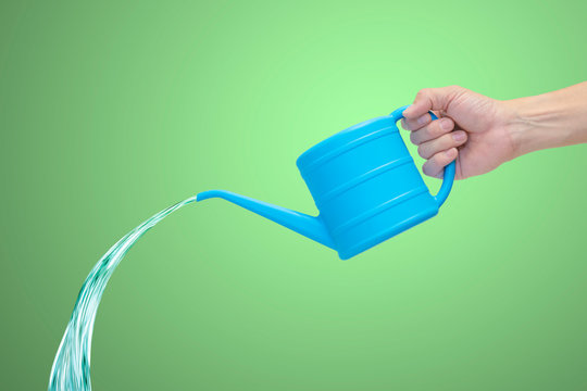 Man's hand holding blue watering can with falling water, isolated on green background.