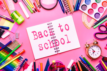 Back to school background with printed text, notebooks, pens, pencils, other stationery on pink modern background, education concept, flat lay, top view