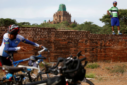 Cyclists take a break and take photos with the ancient pagodas to celebrate Bagan being named as a UNESCO World Heritage Site in Bagan
