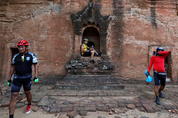 Cyclists take photos with the ancient pagoda to celebrate Bagan being named as as UNESCO World Heritage Site in Bagan