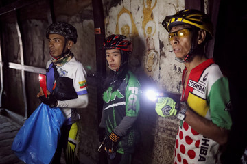Cyclists use the light on their mobile phones to view the ancient drawings inside a pagoda in Bagan, Myanmar