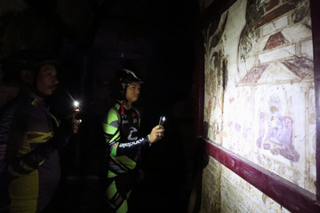 Cyclists use the light on their mobile phones to view the ancient drawings inside a pagoda in Bagan, Myanmar,