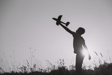 Black and white horizontal image of cute happy kid playing outside with toys. Boy standing in beautiful sunny sunset landscape.