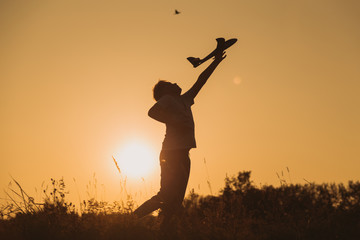 Black silhouette of cute happy cheerful child playing at grassy hill at countryside holding big toy plane in hand. Boy has fun during sunset time in evening. Horizontal color photography.